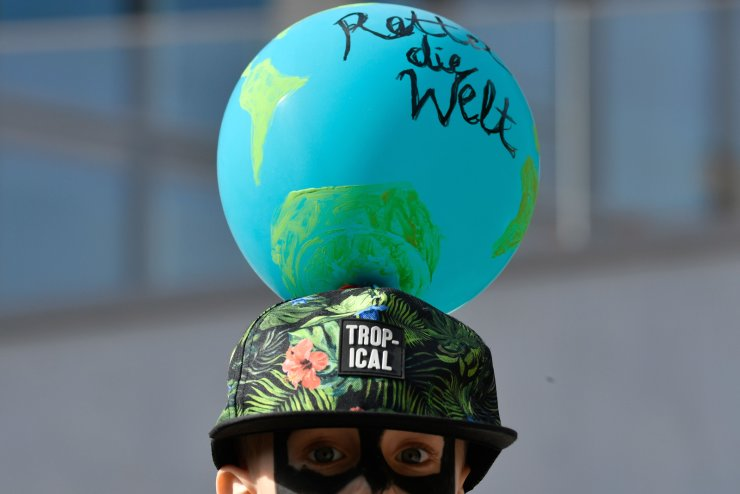 A protester wears a cap with an attached balloon reading 'Save the world' attends the 'Fridays for Future' demonstration in Berlin during a protest for climate action on September 20, 2019, part of a global climate action day. AFP
