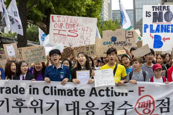 Protesters march toward Cheong Wa Dae after the sports day-themed demonstration in front of the foreign ministry building. Students carry pickets that condemn the Korean government for responding poorly to the climate change issue. The government is rated 'F' for countering the problem and '0' for 'discerning the issue's significance; willingness to solve the issue; and reliability and practicality.' Korea Times photo by Shim Hyun-chul