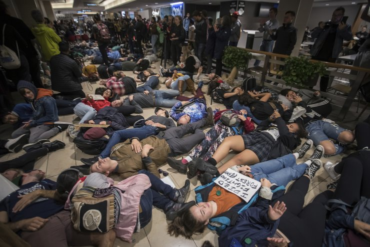 People participating in a 'die-in' climate action protest lie on the floor in the food court of a shopping center in downtown Vancouver on Friday, Sept. 20, 2019. AP