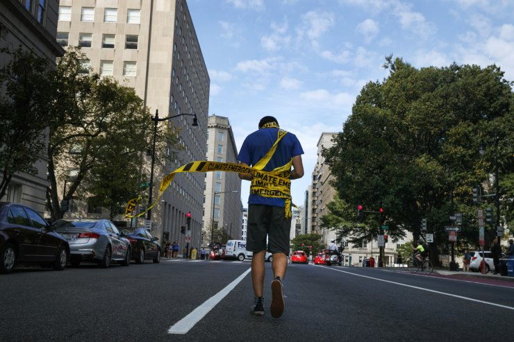 Gabriel Shapiro, of Washington, is wrapped in caution tape that says 'Climate Emergency' as he walks down I Street in NW Washington where traffic was stopped by demonstrations for climate action, Monday, Sept. 23, 2019, in Washington, part of the 'Shut Down DC' protest to urge action on the climate crisis. AP