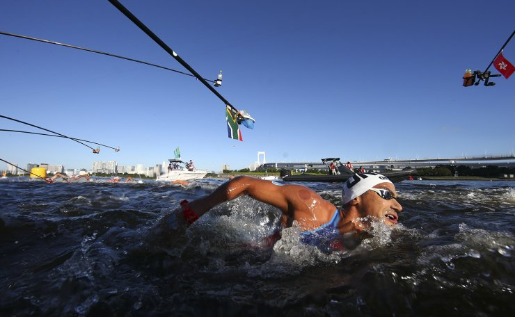 Tokyo 2020 Olympics - Open Water Swimming - Men's 10km - Final - Odaiba Marine Park - Tokyo, Japan - August 5, 2021. Oussama Mellouli of Tunisia swims past bottles of water offered to competitors during the race. REUTERS