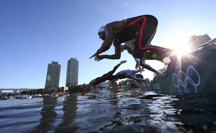 Tokyo 2020 Olympics - Open Water Swimming - Men's 10km - Final - Odaiba Marine Park - Tokyo, Japan - August 5, 2021. Competitors jump into the water at the start of the race. REUTERS