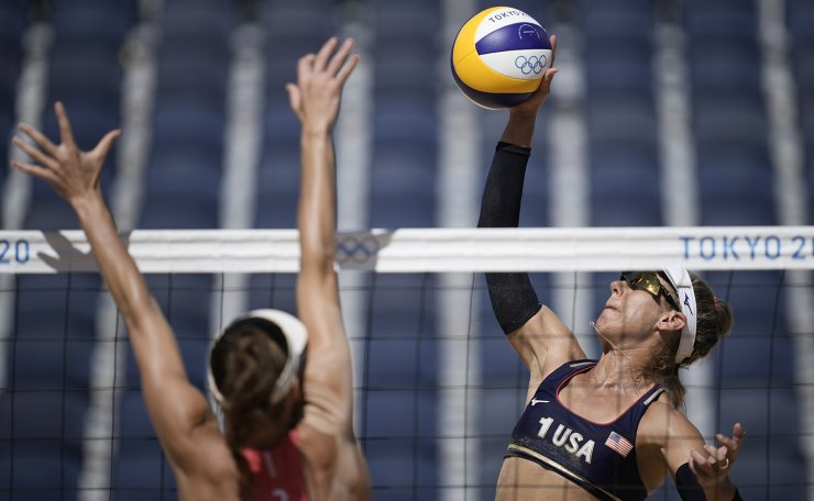 April Ross, right, of the United States, takes a shot as Joana Heidrich, of Switzerland, defends during a women's beach volleyball match against at the 2020 Summer Olympics, Thursday, Aug. 5, 2021, in Tokyo, Japan. AP