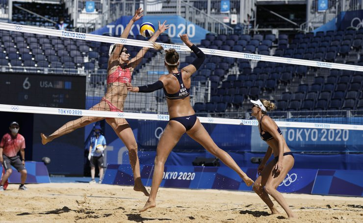 April Ross, center, of the United States, hits a shot as teammate Alix Klineman, right, watches while Joana Heidrich, of Switzerland, defends during a women's beach volleyball semifinal match 03at the 2020 Summer Olympics, Thursday, Aug. 5, 2021, in Tokyo, Japan. AP