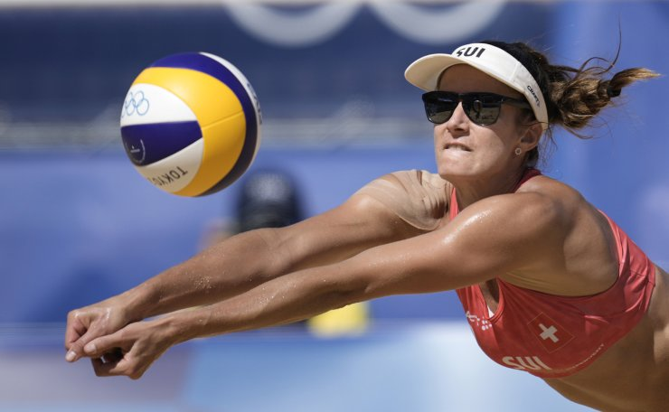 Joana Heidrich, of Switzerland, dives for the ball during a women's beach volleyball semifinal match against Switzerland at the 2020 Summer Olympics, Thursday, Aug. 5, 2021, in Tokyo, Japan. AP