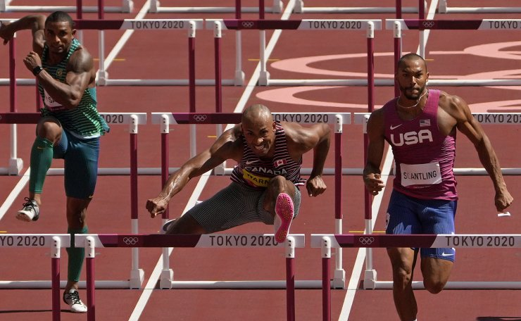 Damian Warner, of Canada clears a hurdle alongside Garrett Scantling, of United States in a heat of the decathlon men's 110-meter hurdles at the 2020 Summer Olympics, Thursday, Aug. 5, 2021, in Tokyo, Japan. AP