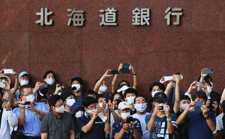 Tokyo 2020 Olympics - Athletics - Women's Marathon - Sapporo Odori Park, Sapporo, Japan - August 7, 2021. Spectators wearing protective face masks watching the competition. REUTERS