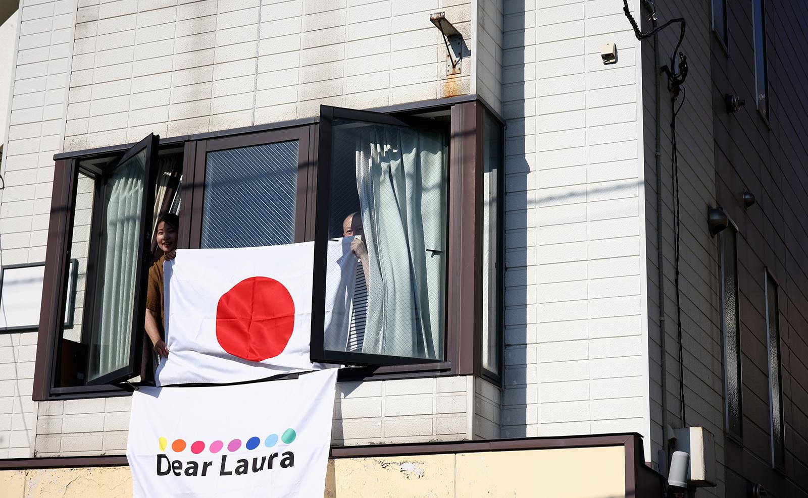 Tokyo 2020 Olympics - Athletics - Women's Marathon - Sapporo Odori Park, Sapporo, Japan - August 7, 2021. Supporters hold a Japanese flag. REUTERS