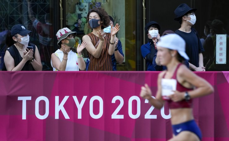 Spectators watch as runners pass in the women's marathon at the 2020 Summer Olympics, Saturday, Aug. 7, 2021, in Sapporo, Japan AP