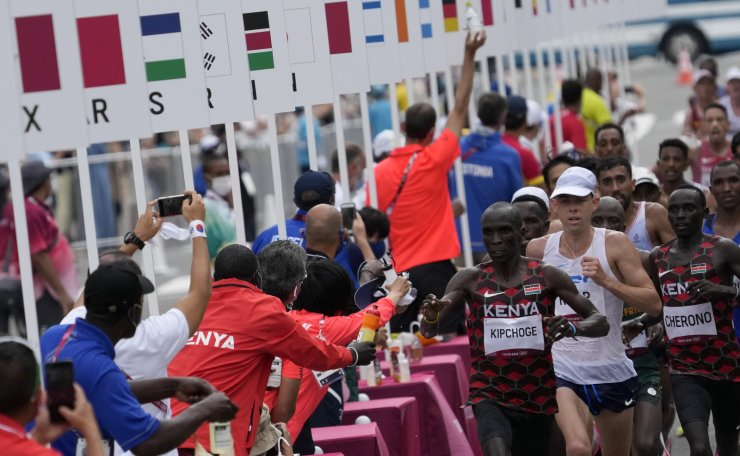 Competitors run past the water station during the men's marathon at the 2020 Summer Olympics, Sunday, Aug. 8, 2021, in Sapporo, Japan.  AP