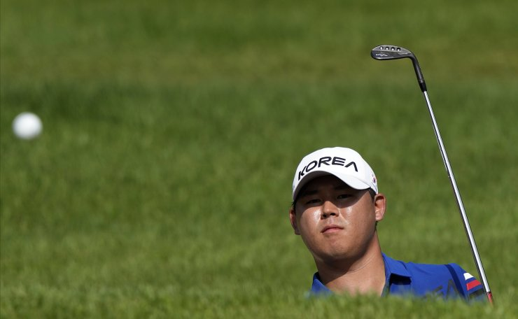Si Woo Kim of Korea watches his shot from a bunker on the fourth hole during the second round of the men's golf event at the 2020 Summer Olympics on Thursday, July 29, 2021, at the Kasumigaseki Country Club in Kawagoe, Japan. AP
