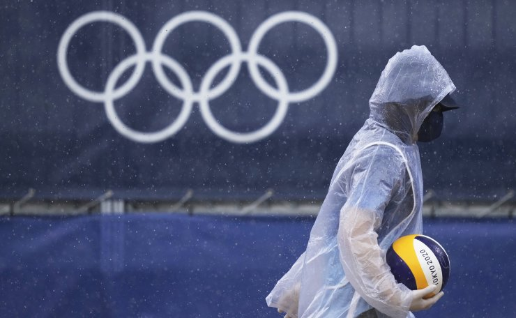 A worker carries a volleyball in the Raine prior to a women's beach volleyball match at the 2020 Summer Olympics, Friday, July 30, 2021, in Tokyo, Japan. AP