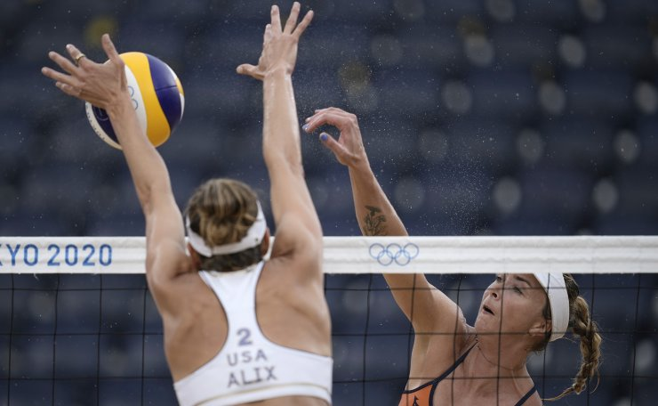 Madelein Meppelink, right, of the Netherlands, takes a shot as Alix Klineman, of the United States, defends during a women's beach volleyball match at the 2020 Summer Olympics, Friday, July 30, 2021, in Tokyo, Japan. AP