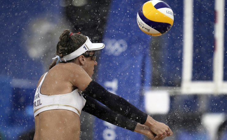 April Ross, of the United States, returns a shot in the rain during a women's beach volleyball match against the Netherlands at the 2020 Summer Olympics, Friday, July 30, 2021, in Tokyo, Japan. AP