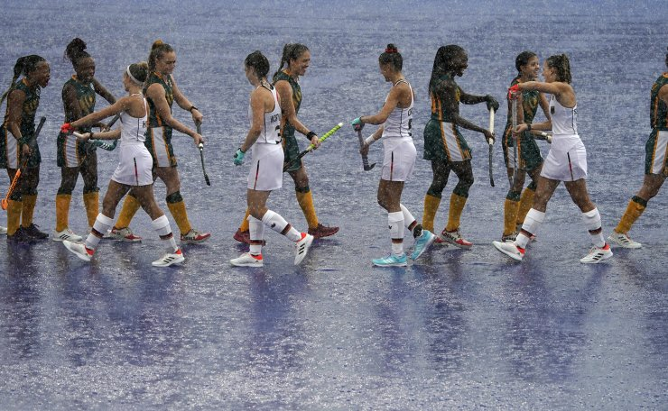 South Africa and Germany players greet each other before their women's field hockey match was delayed because of rain at the 2020 Summer Olympics, Friday, July 30, 2021, in Tokyo, Japan. AP