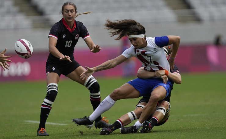 France's Coralie Bertrand makes the pass as she is tackled by Canada's Karen Paquin, in their women's rugby sevens match at the 2020 Summer Olympics, Friday, July 30, 2021 in Tokyo, Japan. AP