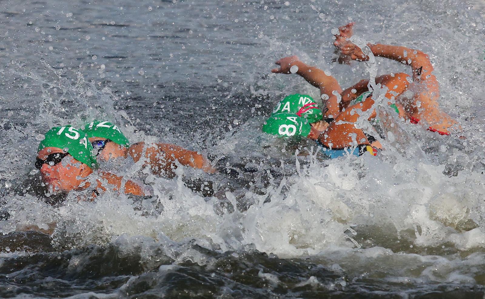 Tokyo 2020 Olympics - Triathlon - Mixed Team Relay - Final - Odaiba Marine Park, Tokyo, Japan - July 31, 2021. Zsanett Bragmayer of Hungary, Yuko Takahashi of Japan, Claire Michel of Belgium and Ainsley Thorpe of New Zealand in action. REUTERS
