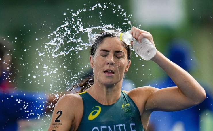 Ashleigh Gentle of Australia cools off during the run as she competes during the mixed relay triathlon at the 2020 Summer Olympics, Saturday, July 31, 2021, in Tokyo, Japan. AP