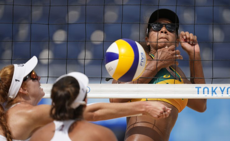 Ana Patricia Silva Ramos, right, of Brazil, waits for the shot of Sarah Sponcil, left, of the United States, as teammate Kelly Claes watches during a women's beach volleyball match at the 2020 Summer Olympics, Saturday, July 31, 2021, in Tokyo, Japan. AP