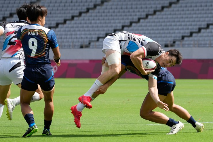 South Korea's Coquillard Andre Jin, top, is tackled by Japan's Chihito Matsui in their men's rugby sevens 11-12 placing match at the 2020 Summer Olympics, Wednesday, July 28, 2021 in Tokyo, Japan. AP
