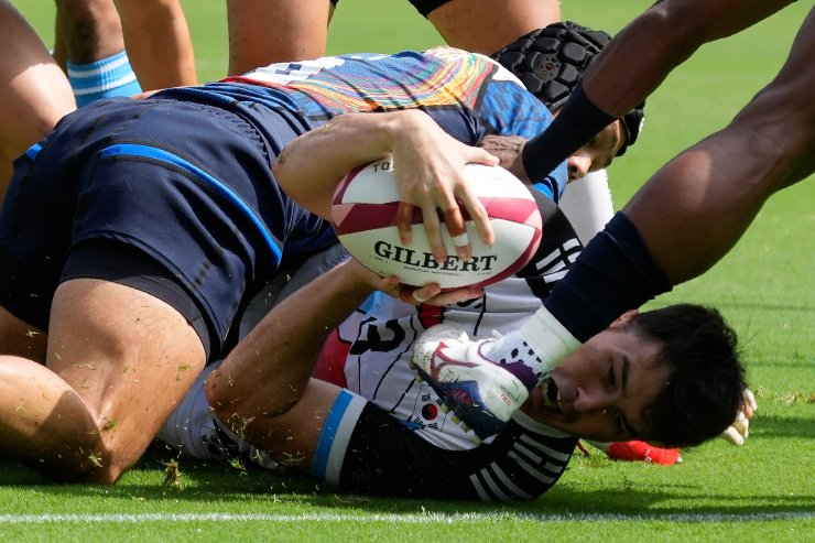 South Korea's Coquillard Andre Jin, bottom, wrestles with Japan's Masakatsu Hikosaka in their men's rugby sevens 11-12 placing match at the 2020 Summer Olympics, Wednesday, July 28, 2021 in Tokyo, Japan. AP