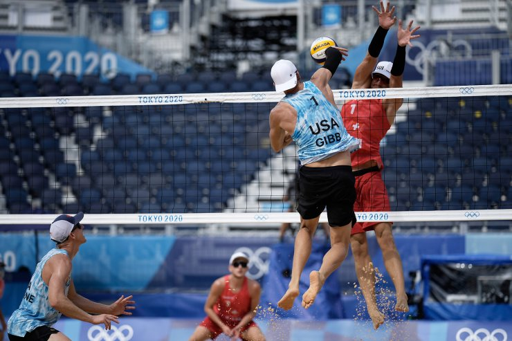 Jacob Gibb, top left, of the United States, takes a shot as Adrian Heidrich, of Switzerland, defends during a men's beach volleyball match at the 2020 Summer Olympics, Wednesday, July 28, 2021, in Tokyo, Japan. AP