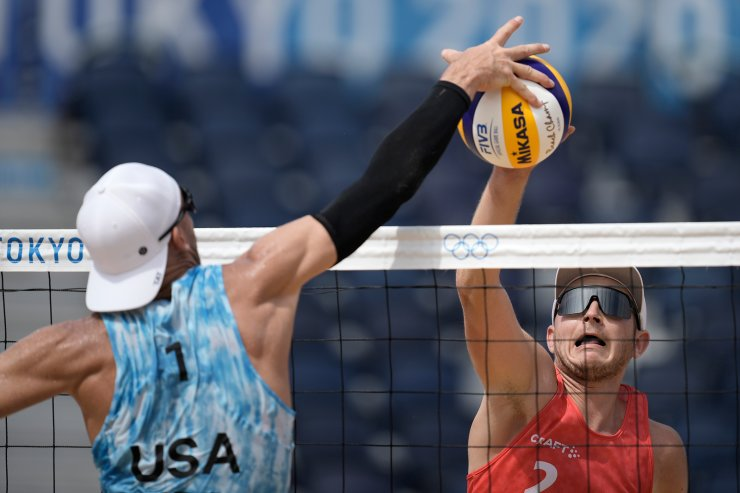 Mirco Gerson, right, of Switzerland, hits the ball as Jacob Gibb, of the United States, defends during a men's beach volleyball match at the 2020 Summer Olympics, Wednesday, July 28, 2021, in Tokyo, Japan. AP