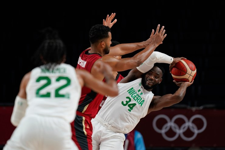 Nigeria's Ike Nwamu (34), right, is blocked by Germany's Johannes Thiemann (32), center, during men's basketball preliminary round game at the 2020 Summer Olympics, Wednesday, July 28, 2021, in Saitama, Japan. AP