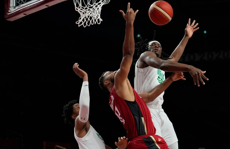 Germany's Johannes Thiemann (32), center, shoots between Nigeria's Chikezie Okpala (0), left, and Precious Achiuwa (55) during men's basketball preliminary round game at the 2020 Summer Olympics, Wednesday, July 28, 2021, in Saitama, Japan. AP