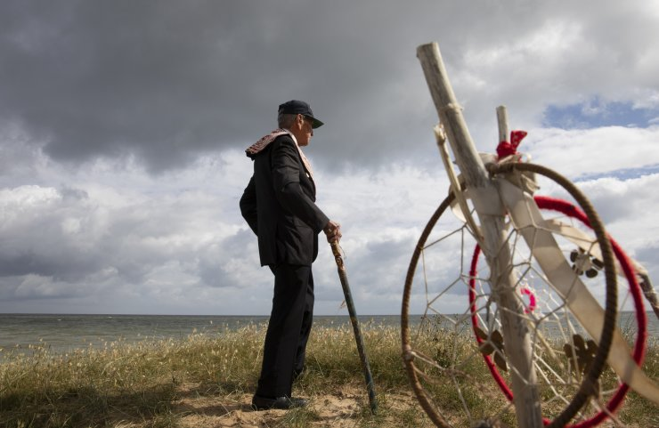 World War II D-Day veteran and Penobscot Elder from Maine, Charles Norman Shay stands near Native American dreamcatchers as he looks out over a dune on Omaha Beach prior to a ceremony at his memorial in Saint-Laurent-sur-Mer, Normandy, France, Friday, June 5, 2020. Saturday's anniversary of D-Day will be one of the loneliest remembrances ever, as the coronavirus pandemic is keeping almost everyone away, from government leaders to frail veterans who might not get another chance for a final farewell to their unlucky comrades. AP