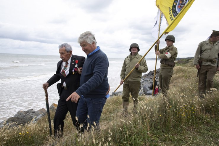 World War II D-Day veteran and Penobscot Elder from Maine, Charles Norman Shay, left, walks in the dunes overlooking Omaha Beach with men in WWII period uniforms after a Native American ceremony at his memorial in Saint-Laurent-sur-Mer, Normandy, France, Friday, June 5, 2020. AP