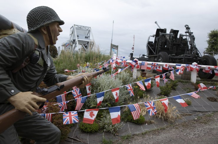 A mannequin dressed in WWII is posed in a charge position among French, British, Canadian and American flags at the site of the original WWII Pegasus Bridge in Benouville, Normandy, France, Friday, June 5, 2020. Saturday's anniversary of D-Day will be one of the loneliest remembrances ever, as the coronavirus pandemic is keeping almost everyone away, from government leaders to frail veterans who might not get another chance for a final farewell to their unlucky comrades. The current bridge was built in 1994 while the original is on display at a local museum. AP