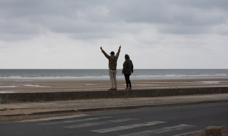 In this photo taken on Thursday, June 4, 2020, A man and woman in US military jackets stand in front of Omaha Beach in Saint-Laurent-sur-Mer, Normandy, France. In sharp contrast to the 75th anniversary of D-Day, this year's 76th will be one of the loneliest remembrances ever, as the coronavirus pandemic is keeping nearly everyone from traveling. AP