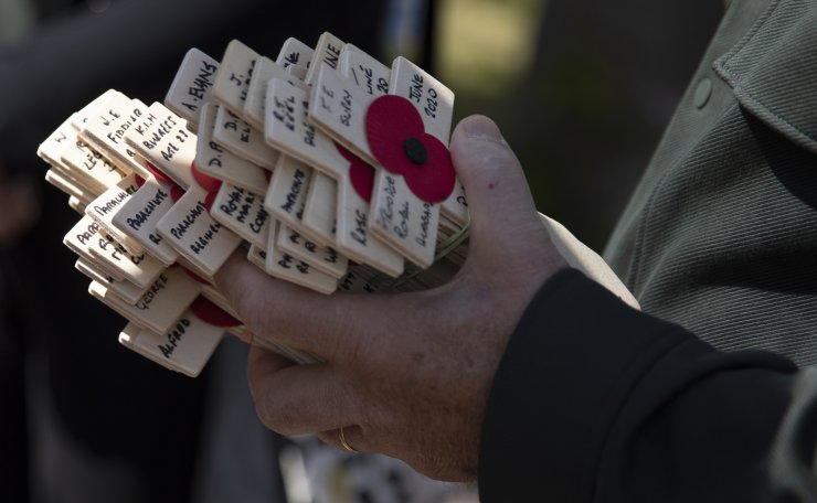 Wooden crosses with names of WWII dead are held prior to being laid for the Portsmouth Trust group by British expatriate Steven Oldrid during D-Day ceremonies at the local war cemetery in Benouville, Normandy, France on Saturday, June 6, 2020. Due to coronavirus measures many relatives and veterans will not make this years 76th anniversary of D-Day. Oldrid will be bringing it to them virtually as he places wreaths and crosses for families and posts the moments on his facebook page. AP