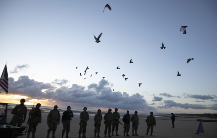 Men in a vintage US WWII uniform watch as pigeons are released during a D-Day 76th anniversary ceremony in Saint Laurent sur Mer, Normandy, France, Saturday, June 6, 2020. Due to coronavirus measures many ceremonies and memorials have been cancelled in the region with the exception of very small gatherings. AP