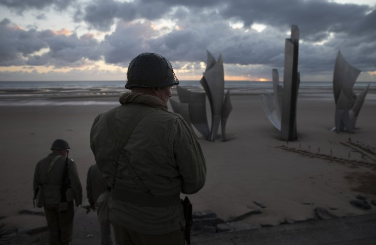 Two men in vintage US WWII uniforms walk toward the Les Braves monument at sunrise prior to a D-Day 76th anniversary ceremony in Saint Laurent sur Mer, Normandy, France, Saturday, June 6, 2020. AP