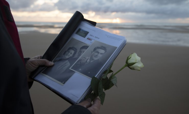 Billie Bishop, from San Jose, California, holds a photo of his uncle, WWII soldier Billie Bishop, as he prepares to lay a rose in the sea during a D-Day 76th anniversary ceremony in Saint Laurent sur Mer, Normandy, France, Saturday, June 6, 2020. AP
