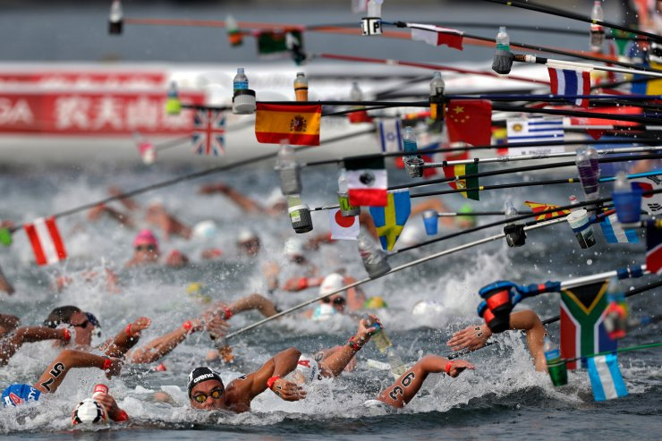 Swimmers reach for drink bottles while competing in the men's 10km open water swim at the World Swimming Championships in Yeosu, South Korea, Tuesday, July 16, 2019. AP