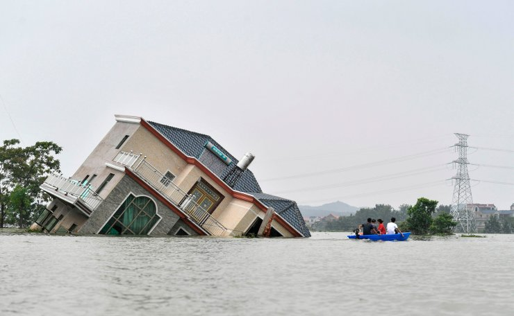 This photo taken on July 15, 2020 shows residents riding a boat past a damaged and flood-affected house near the Poyang Lake due to torrential rains in Poyang county, Shangrao city in China's central Jiangxi province. The vast Yangtze drainage area has been lashed by torrential rains since last month, leaving 141 people dead or missing and forcing the evacuation of millions more across several provinces. AFP
