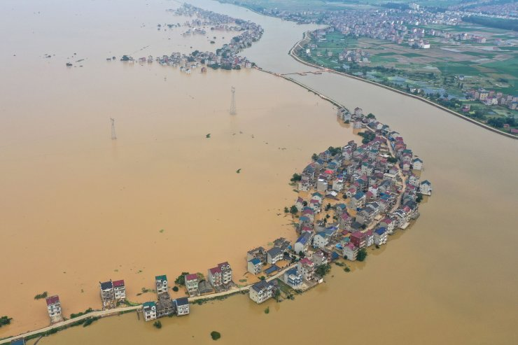 This aerial view shows submerged streets and inundated buildings after a dam was breached due to flooding in Jiujiang in China's central Jiangxi province on July 13, 2020. AFP