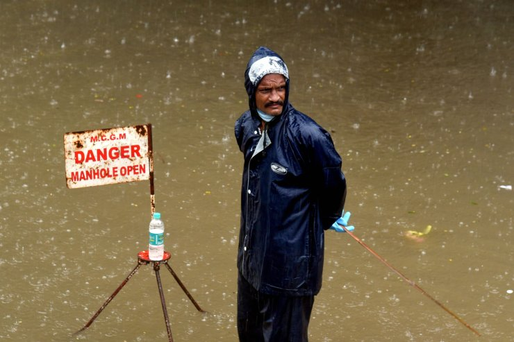 A municipal worker stands on a flooded road to guide vehicles during a rain shower in Mumbai on July 15, 2020. AFP