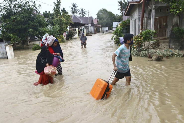 People carry their belongings as they wade through water in an area affected by flash floods in Luwu Utara, South Sulawesi province, Indonesia, Thursday, July 16, 2020. A number of people were killed and missing after heavy rains in the South Sulawesi province swelled rivers and send floodwaters, mud and debris across roads and into thousands of homes. AP