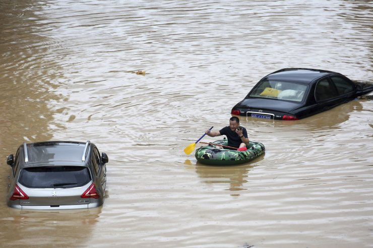 a man paddles with an inflatable boat past submerged cars during a flood in Rongshui County in southern China's Guangxi Zhuang Autonomous Region, Saturday, July 11, 2020. Vice Minister of Emergency Management Zheng Guoguang told reporters Monday, July 13, 2020 that the Yangtze River and parts of its watershed have seen the second highest rainfall since 1961 over the past six months. Xinhua