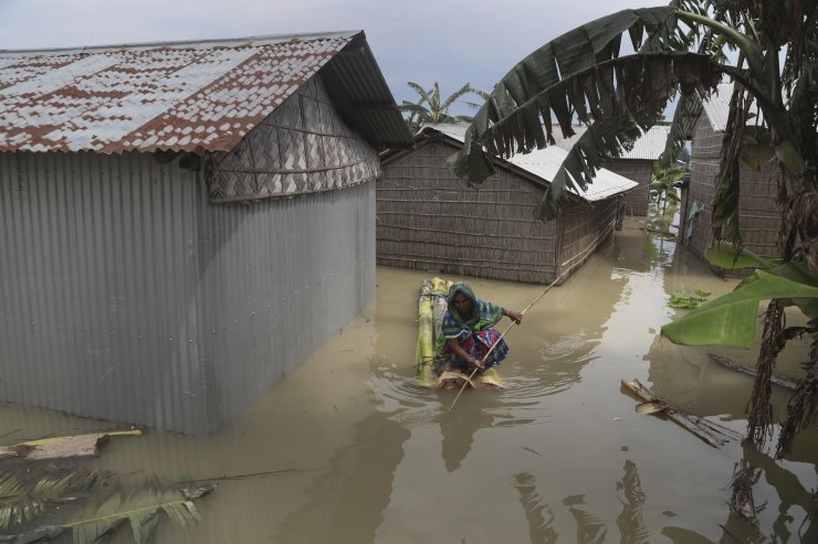 An Indian flood affected woman rows a makeshift banana raft near her partially submerged house in Gagolmari village, Morigaon district, Assam, India, Tuesday, July 14, 2020. Hundreds of thousands of people have been affected by floodwaters and landslides following incessant rainfall in the region. AP