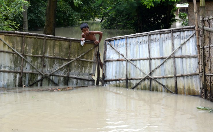 A child climbs over a fence submerged in flood water in Morigaona district of Assam, India, 15 July 2020. According to news reports, heavy rainfall during the past days have caused floods in the Assam state, leaving over three million people affected by it and at least sixty dead. EPA