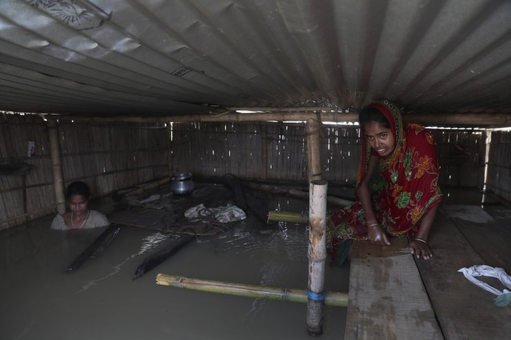 Indian flood affected villagers are seen inside their partially submerged houses in Gagolmari village, Morigaon district, Assam, India, Tuesday, July 14, 2020. Hundreds of thousands of people have been affected by floodwaters and landslides following incessant rainfall in the region. AP