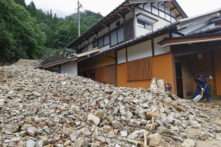 A resident cleans earth and sand slid into the front of a house following a heavy rain in Gero, Gifu prefecture, central Japan Thursday, July 9, 2020. Flooding and mudslides have stranded hundreds of people in scenic hot springs and hiking areas in central Japan, while rescue workers searched on Thursday for more people missing in the disaster. AP