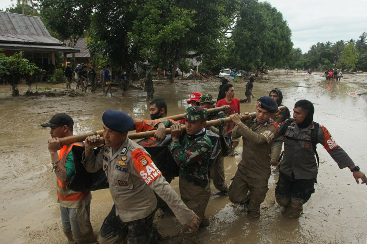 A rescue team carry a victim's body following flash flooding in Radda village in North Luwu regency, South Sulawesi on July 14, 2020, after three rivers overflowed due to torrential rains. - At least 15 people died and dozens others were missing after flash floods caused by torrential rains left hundreds of houses buried in mud in Indonesia, authorities said. AFP
