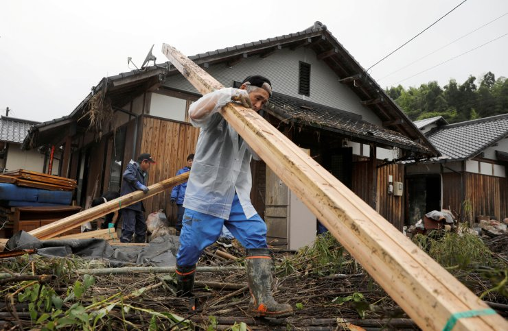 A man carries debris from a damaged house, after floods caused by torrential rain swept through Kumamura, Kumamoto Prefecture, southwestern Japan, July 9, 2020. REUTERS