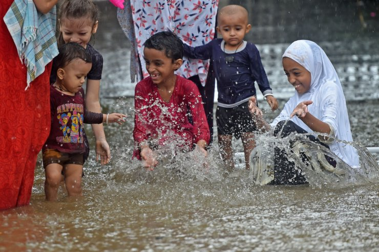 Children play in a flooded street during a rain shower in Mumbai on July 15, 2020. - The monsoon -- which usually falls from June to September -- is crucial to the economy of the Indian sub-continent, but also causes widespread death and destruction across the region each year. AFP
